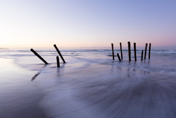The South Pacific Ocean swirls through the lastr remaining remnants of the iconic poles at St Clair Beach, Dunedin, New Zealand.